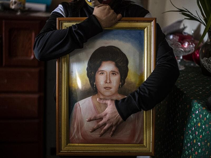 Peruvian Liset Diaz, 35, holds a painting of her grandmother Edita Leiva -in her youth-, 76, who died from COVID-19 at her home in Chorrillos, south of Lima, Peru on August 11, 2020. Global deaths from the coronavirus have almost reached on September 25, 2020 the grim threshold of one million. Around one-third of fatalities were in Latin America, where countries with overstretched medical resources are preparing for a further onslaught. ERNESTO BENAVIDES / AFP