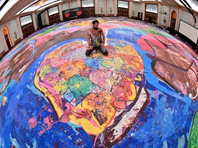 Contemporary British artist Sacha Jafri (C) stands on his record-breaking painting entitled 'The Journey of Humanity' on September 23, 2020, in the Emirati city of Dubai. The painting, which measures the size of two football fields, can be seen at a hotel in Dubai, where Jafri spent months of lockdown due to the coronavirus pandemic. The gigantic artwork is part of his project 'Humanity Inspired' and with it he hopes to raise 30 million USD to fund health and education initiatives for children living in pov