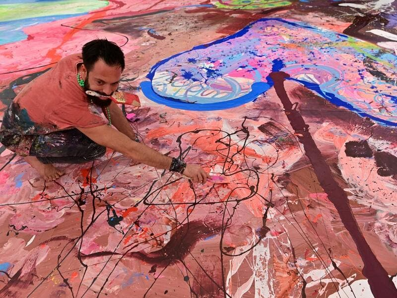 Contemporary British artist Sacha Jafri works on his record-breaking painting entitled 'The Journey of Humanity' on September 23, 2020, in the Emirati city of Dubai. The painting, which measures the size of two football fields, can be seen at a hotel in Dubai, where Jafri spent months of lockdown due to the coronavirus pandemic. The gigantic artwork is part of his project 'Humanity Inspired' and with it he hopes to raise 30 million USD to fund health and education initiatives for children living in poverty