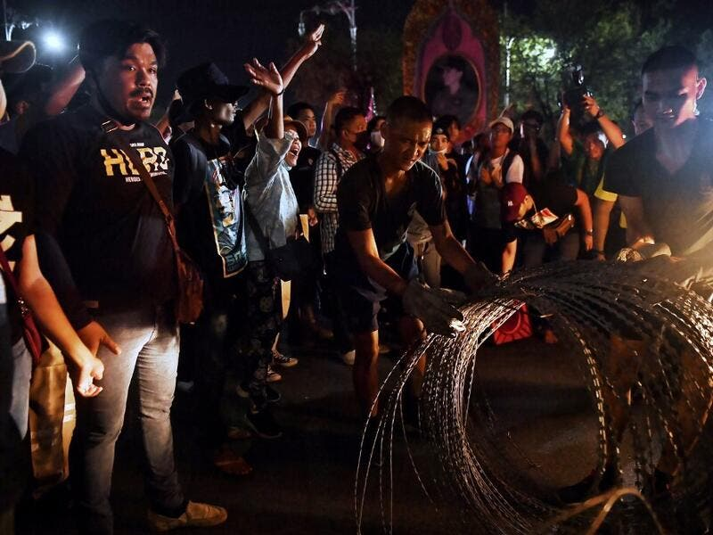 Pro-democracy protesters heckle soldiers as they are deterred from installing razor wire on the road in front of the Royal Thai Army headquarters in Bangkok on October 14, 2020. Lillian SUWANRUMPHA / AFP