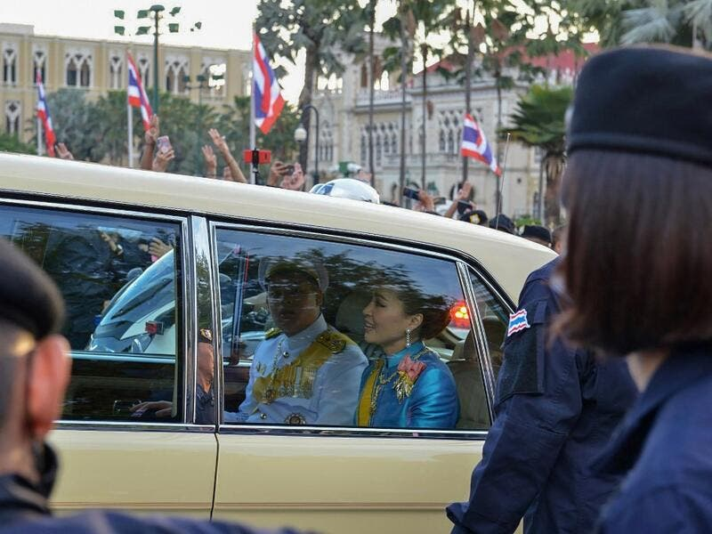 Thailand's Queen Suthida (C) and Prince Dipangkorn Rasmijoti (centre L) react inside a royal motorcade as it drives past a pro-democracy rally, as anti-government protesters (back) hold up their three-finger salute, in Bangkok on October 14, 2020. Teera NOISAKRAN / AFP