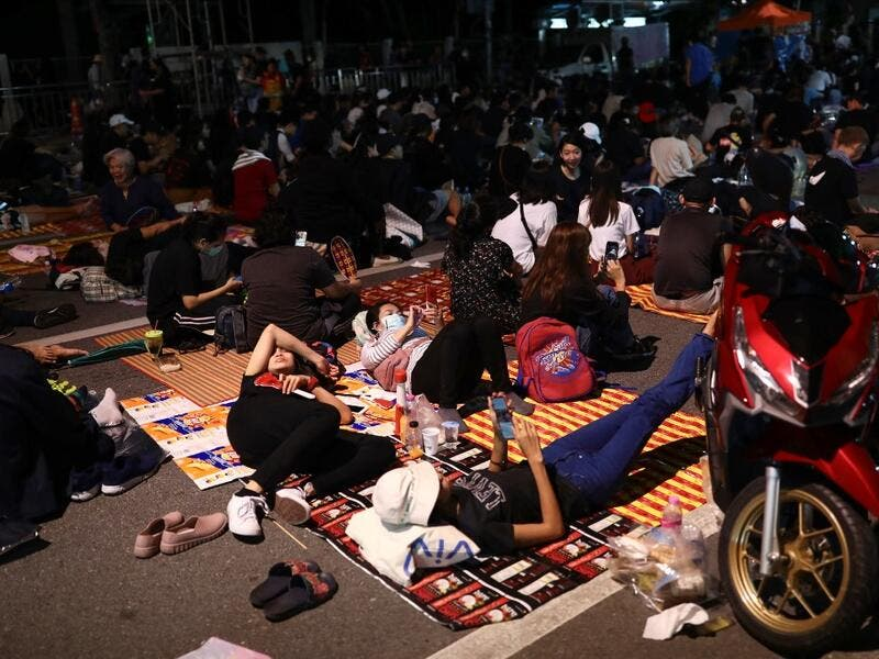 Pro-democracy protesters rest on the ground during an anti-government rally next to Government House in Bangkok on October 14, 2020. Jack TAYLOR / AFP