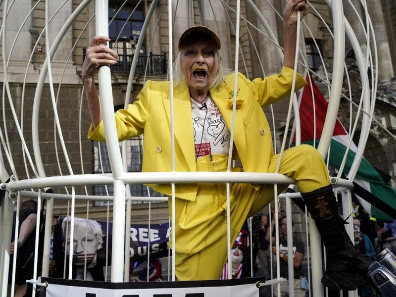 In this file photo taken on July 21, 2020 British designer Vivienne Westwood gestures from inside a giant bird-cage, suspended off the ground, in front Of the Old Bailey in central London on July 21, 2020, in protest of the extradition trial of Wikileaks founder Julian Assange. The legal controversies surrounding the WikiLeaks founder Julian Assange are now in their second decade and the divisions between his supporters and critics remain as intractable as ever. Niklas HALLE'N / AFP