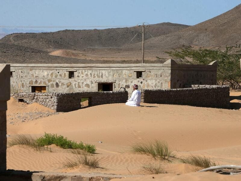 Mohammed al-Ghanbousi, a former inhabitant of Wadi al-Murr, kneels to pray on a sand dune among abandoned houses in the Omani village, about 400 kms (250 miles) southwest of the capital Muscat, on December 31, 2020. MOHAMMED MAHJOUB / AFP