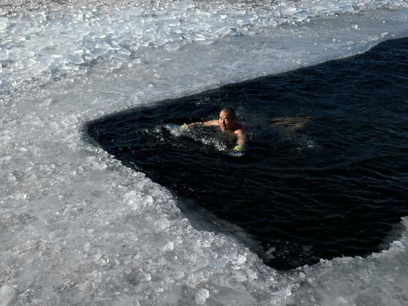 An ice swimmer swims in a frozen lake on a cold winter day in Beijing on January 6, 2021. WANG Zhao / AFP