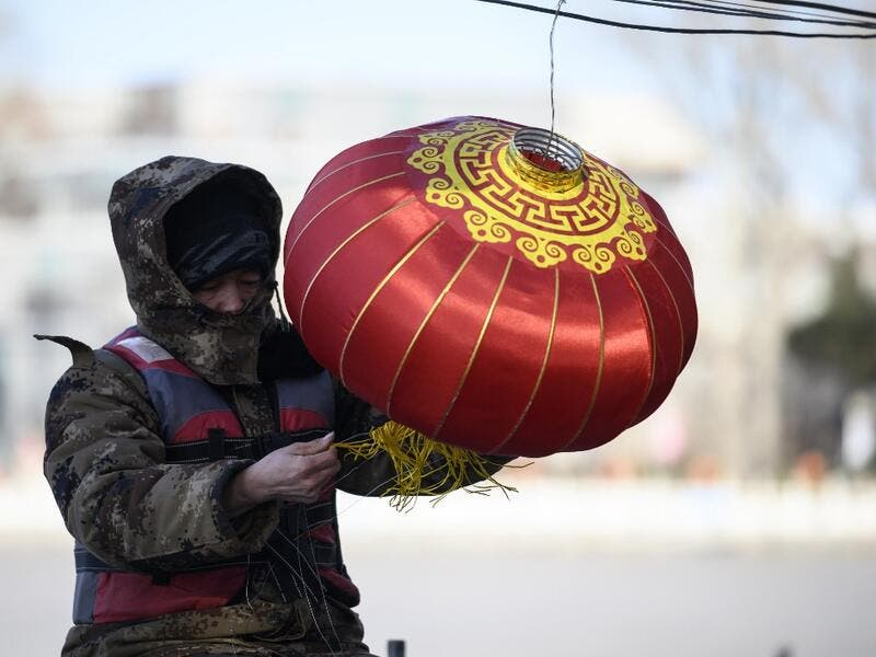 A worker installs a lantern by the icy Lake Houhai in Beijing on January 7, 2021, after China's meteorological authority recently issued a severe weather warning across large parts of the country. NOEL CELIS / AFP