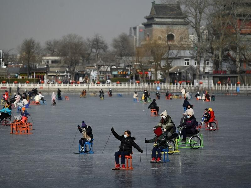 People use sleds on a frozen lake in Beijing on January 12, 2021. WANG Zhao / AFP