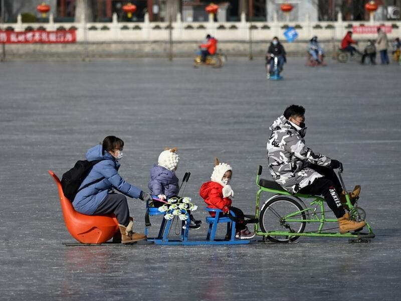 A family uses a sled on a frozen lake in Beijing on January 12, 2021. WANG Zhao / AFP