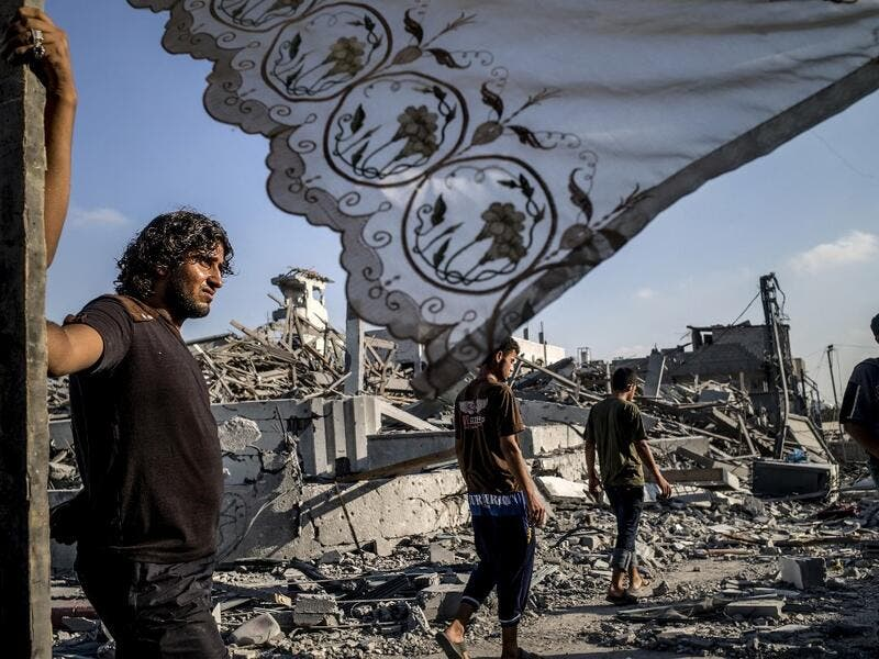 In this file photo taken on August 6, 2014 Palestinians stand next to a makeshift shelter erected outside their destroyed house in the devastated neighbourhood of Shejaiya in Gaza City. MARCO LONGARI / AFP
