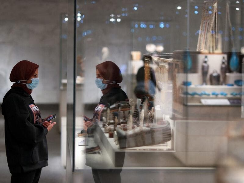 A visitor looks at displayed artifacts at Egypt's new National Museum of Egyptian Civilisation (NMEC)