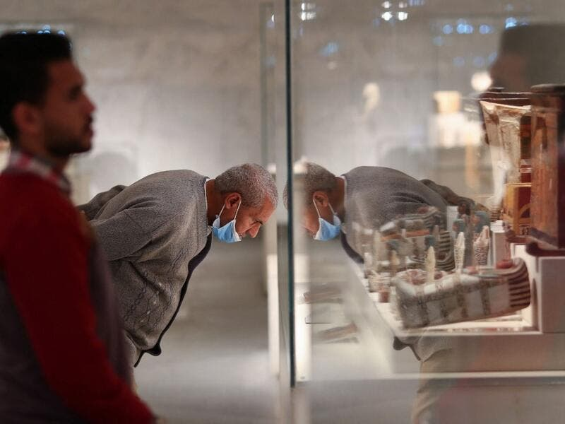 People look at displayed artifacts at Egypt's new National Museum of Egyptian Civilisation (NMEC)