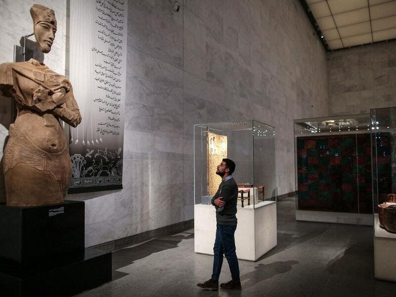 A visitor looks at a large statue of the 18th dynasty Pharaoh Akhenaten at Egypt's new National Museum of Egyptian Civilisation (NMEC)