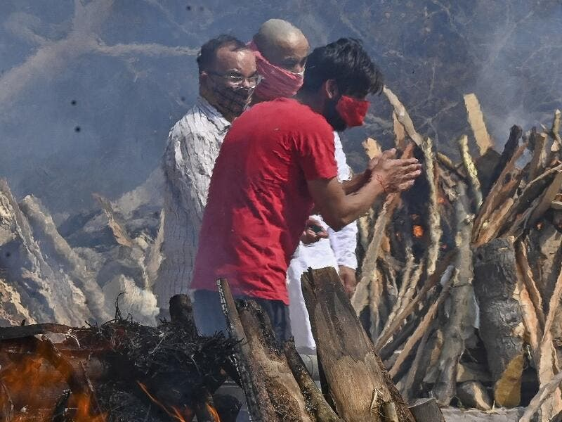 A man reacts as he performs the last rites of his relative amid the funeral pyres of victims who died of the Covid-19 coronavirus during mass cremation held at a crematorium in New Delhi