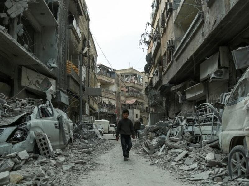 A picture taken on Mar. 8, 2018 shows a Syrian child walking down a street past rubble from destroyed buildings, in the rebel-held town of Douma in the Eastern Ghouta enclave on the outskirts of Damascus.  (HAMZA AL-AJWEH / AFP)