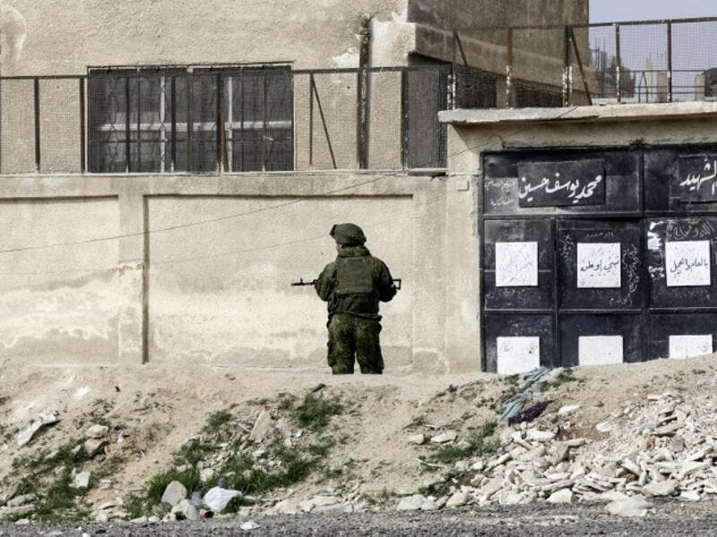 A member of the Russian military police stands guard at the Wafideen checkpoint on the outskirts of the Syrian capital Damascus neighboring the rebel-held Eastern Ghouta enclave on Mar. 13, 2018, awaiting any civilians evacuating from the area.  (Louai Beshara / AFP)
