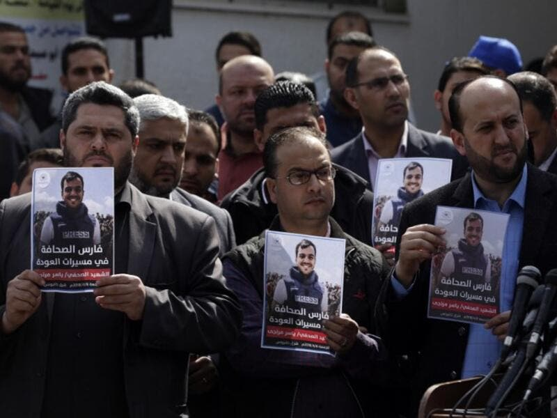 Palestinian journalists carry a portrait of journalist Yasser Murtaja, during his funeral in Gaza City on Apr. 7, 2018. (MAHMUD HAMS / AFP)