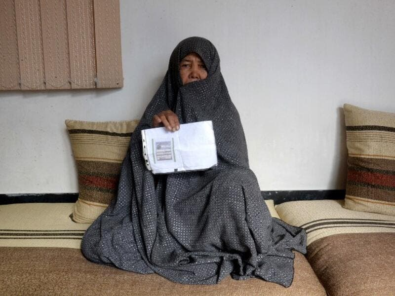 In this photo taken on October 11, 2018. Afghan housewife Fatimah, 55, poses for a picture as she holds her ID card or Tazkira registered to vote in the upcoming parliamentary election, at her House in Mazar-i-Sharif. 
