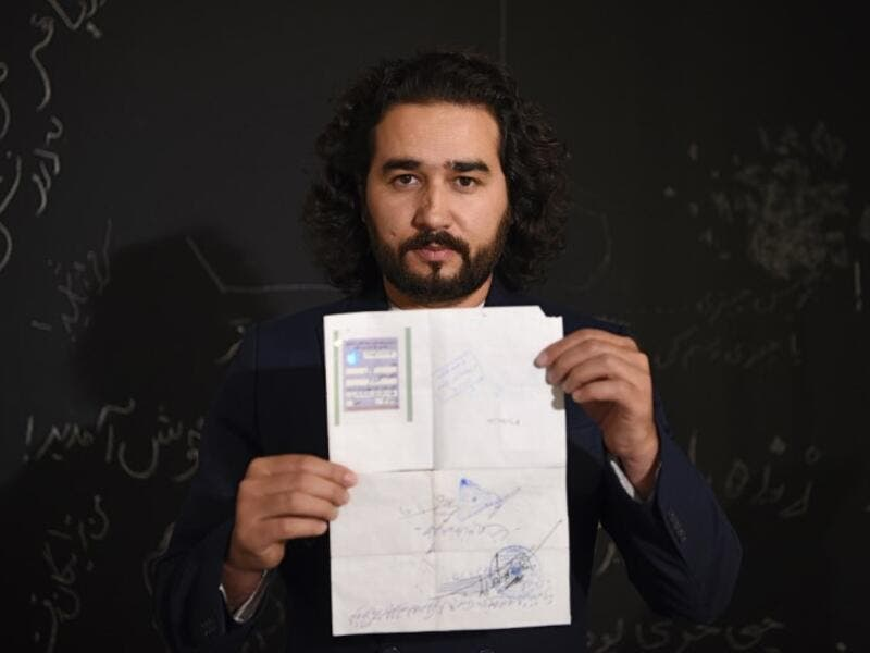 In this photo taken on October 8, 2018, Afghan co-founder and president of ArtLords Omaid Sharifi, 32, poses for a picture as he holds his id card or Tazkira registered to vote in the upcoming parliamentary election, in Kabul. 