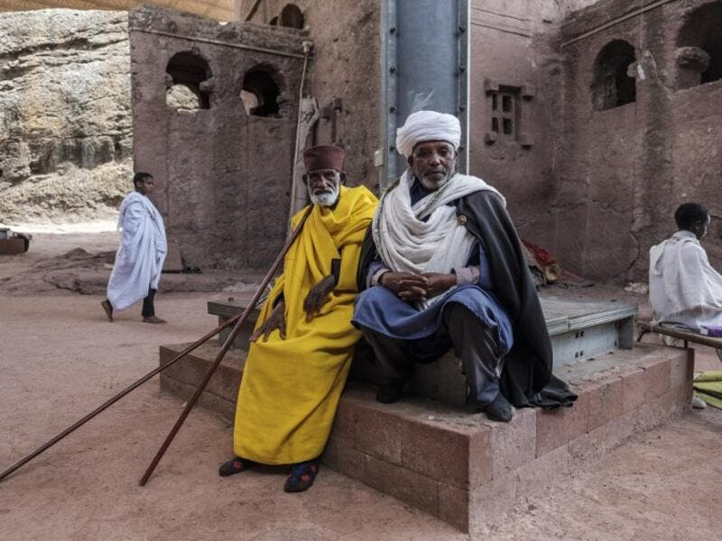 An Ethiopian Orthodox priest Mekonnen Fatne (R) poses near the church of Saint Mary which is covered by a shelter to protect its rock-hewn structure from erosion in Lalibela