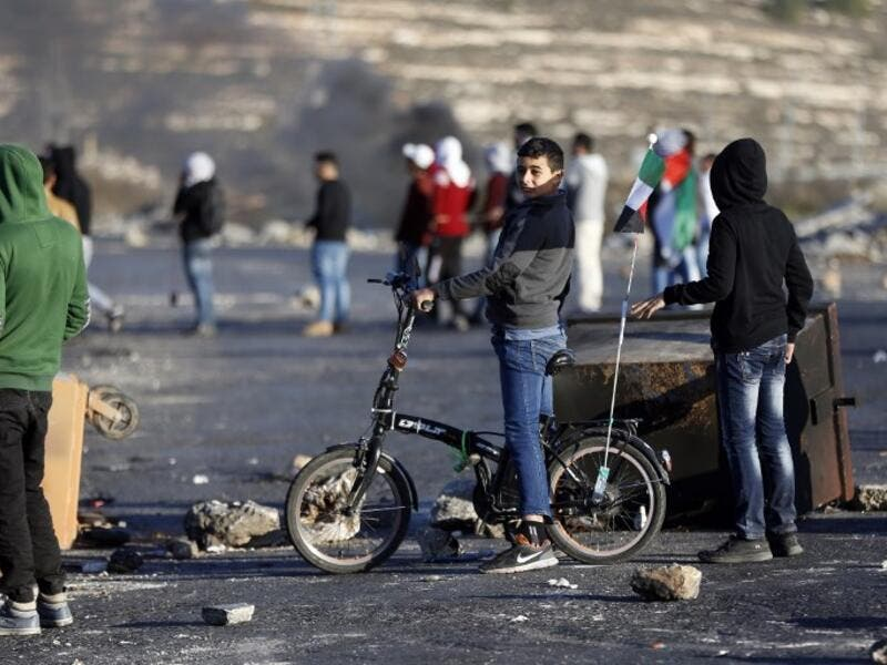 A Palestinian boy rides his bike during clashes with Israeli forces near an Israeli checkpoint in the West Bank city of Ramallah.