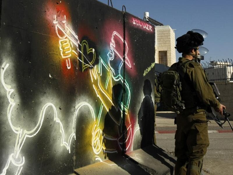 Israeli forces stand guard in front of a mural at the main entrance of Bethlehem, in the Israeli occupied West Bank as protests continue in the region.