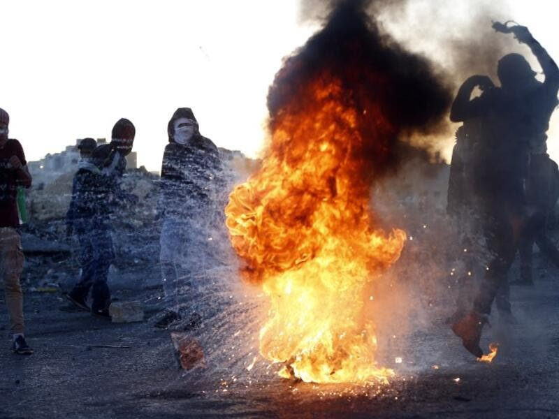 A Palestinian demonstrator kicks a burning tire during clashes with Israeli forces near an Israeli checkpoint in the West Bank city of Ramallah following the U.S. president's controversial recognition of Jerusalem as Israel's capital. 
