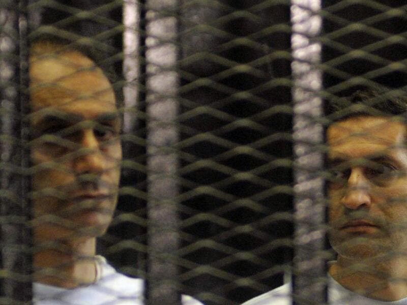Alaa (R) and Gamal Mubarak, sons of ousted Egyptian president Hosni Mubarak, standing inside a cage in a courtroom during their verdict hearing in Cairo. (AFP/File)