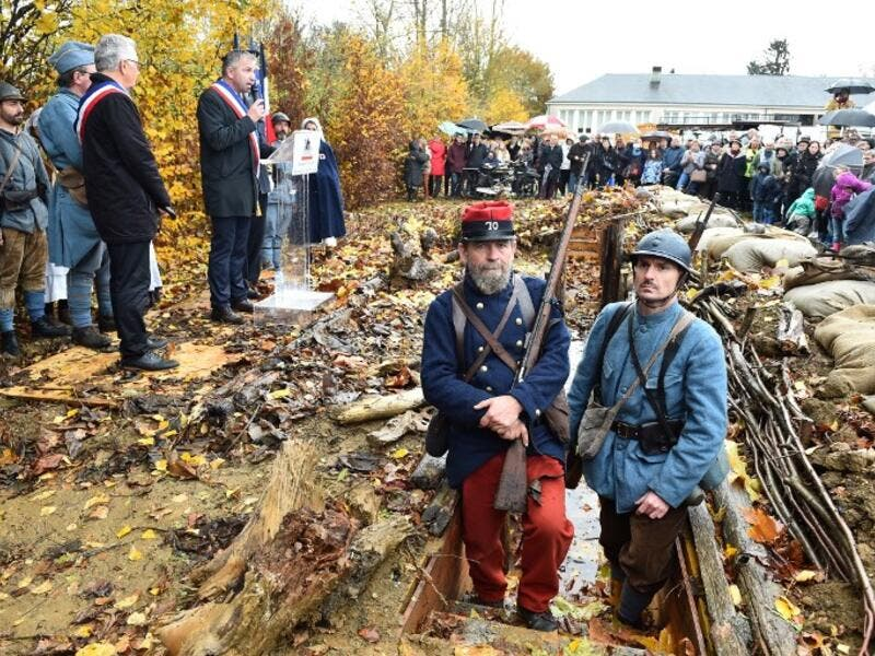Inhabitants of Souille and La Guierche and history enthusiast, dressed with vintage army uniforms of Poilu (French soldier in World War I), stand guard in a reconstructed trench of the WWI, as they take part in a ceremony to inaugurate the trench on November 11, 2018 