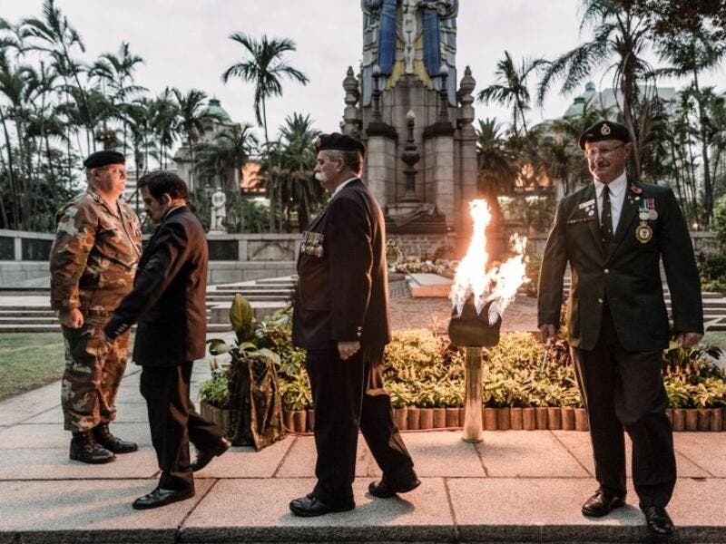 Staff Officers from Defence Reserves of the South African National Defence Force (SANDF) light a gas lamp lit for the Beacon of Light at the Cenotaph in Durban, on November 11, 2018 as part of commemorations marking the 100th anniversary of the 11 November 1918 armistice, ending World War I. 