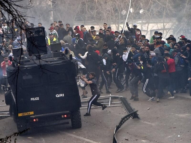 Algerian protesters attempt to overturn a riot police vehicle during clashes in the capital 