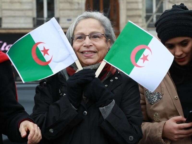 A woman holds Algerian flags during a rally against ailing Algerian president's decision to stand for a fifth term in office