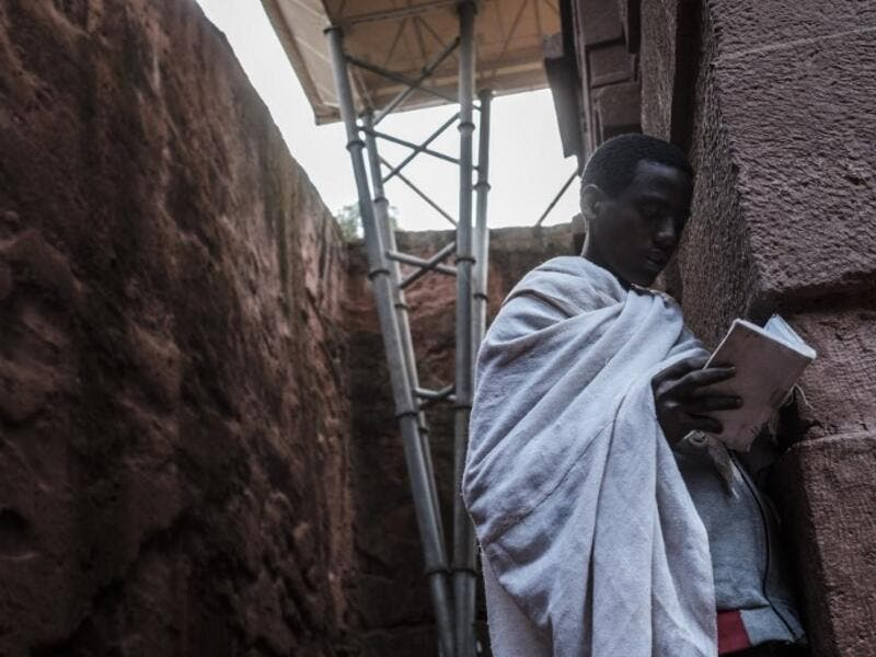 An Ethiopian Orthodox devotee reads a bible near the pillar of a shelter protecting from erosion the rock-hewn structure of the church of Saint Emmanuel in Lalibela, Ethiopia