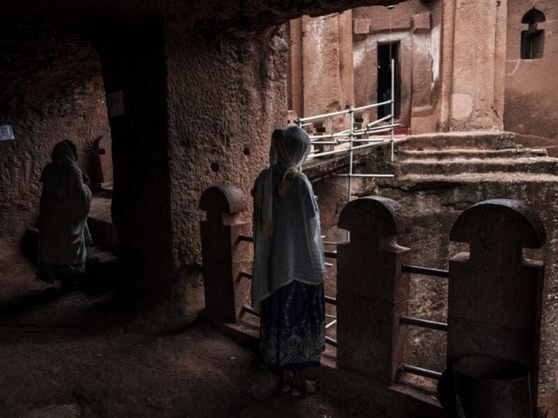 Ethiopian Orthodox devotees stand between the rock-hewn churches of Saint Gabriel and Saint Raphael in Lalibela, Ethiopia