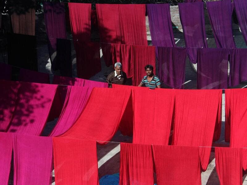 A Pakistani worker dries fabric threads after dyeing them at a factory in Lahore (Twitter)