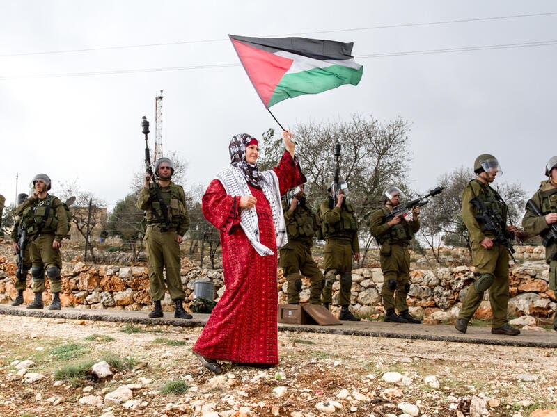 Palestinian woman walks with Palestinian flag (Shutterstock)