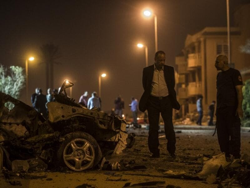 Egyptian officials inspect the wreckage of a car bomb that exploded in a Cairo suburb after Egypt's deputy prosecutor general drove by late on September 29, 2016, wounding a passerby. (AFP/Khaled Desouki)
