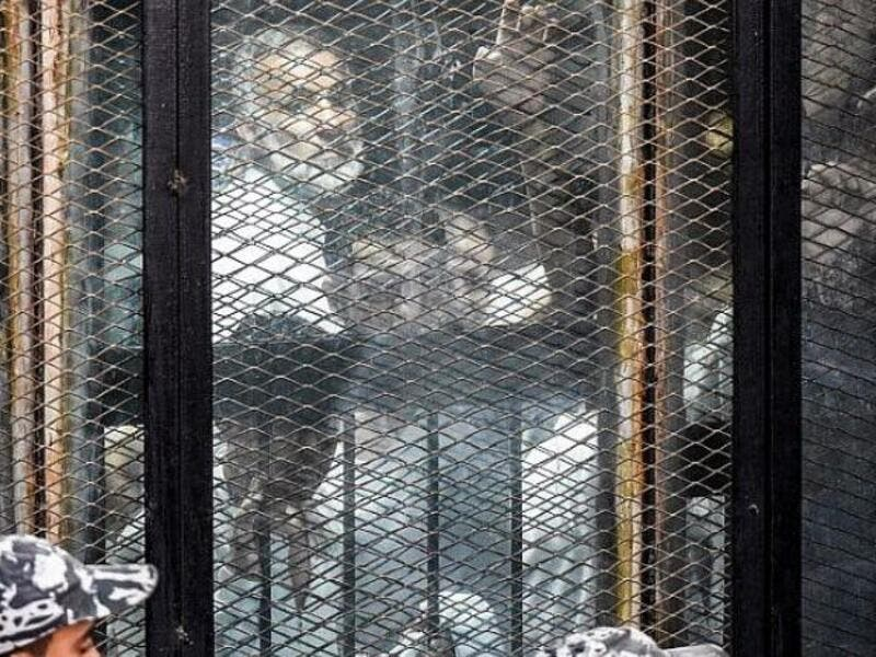 Essam el-Erian (R), one of the highest-ranking leaders of Egypt's banned Muslim Brotherhood, is seen alongside other members of the group inside a glass dock during their trial in the capital Cairo on July 28, 2018. (AFP Photo)