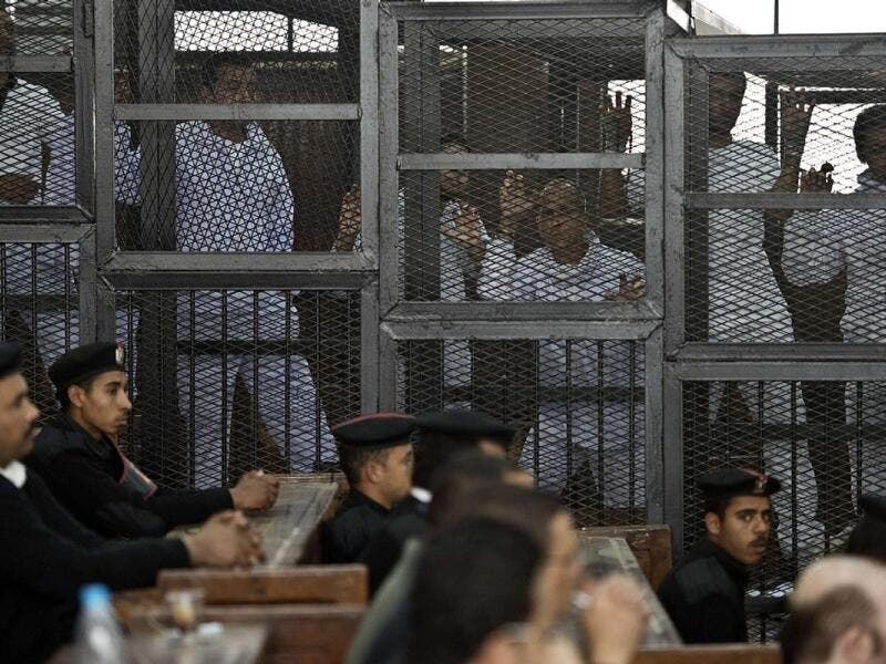 Journalists stand in the defendants' cage in a 2014 trial in Egypt. (AFP/File)