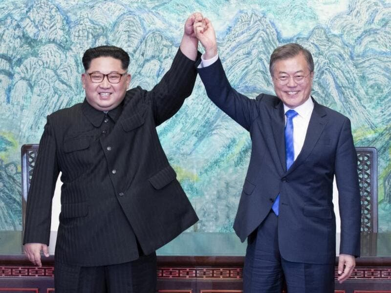 North Korea's leader Kim Jong Un (L) and South Korea's President Moon Jae-in (R) raise their joined hands during a signing ceremony near the end of their historic summit. (AFP/ File Photo)