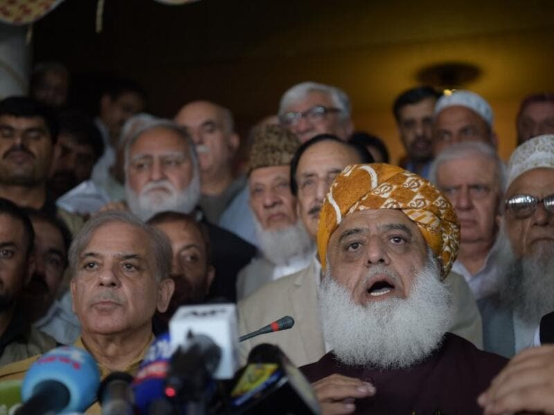 Shahbaz Sharif (R), younger brother of ousted Pakistani Prime Minister Nawaz Sharif and head of Pakistan Muslim League-Nawaz (PML-N), arrive with opposition leader Maulana Fazalur Rehman (L) for a press conference after attending an All Parties Conference in Islamabad on July 27, 2018. (AFP/Aamir Qureshi)