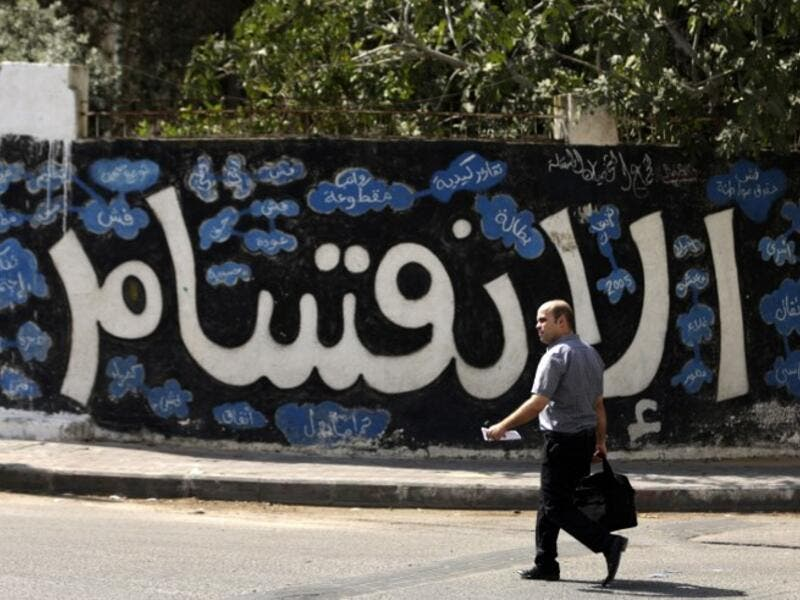 A Palestinian man walks past a graffiti reading in Arabic ''Division'' in Gaza City, on September 17, 2017, after Hamas announced it had agreed to steps toward resolving a decade-long split with the Fatah movement and was ready to hold elections (Mahmud Hams/AFP)