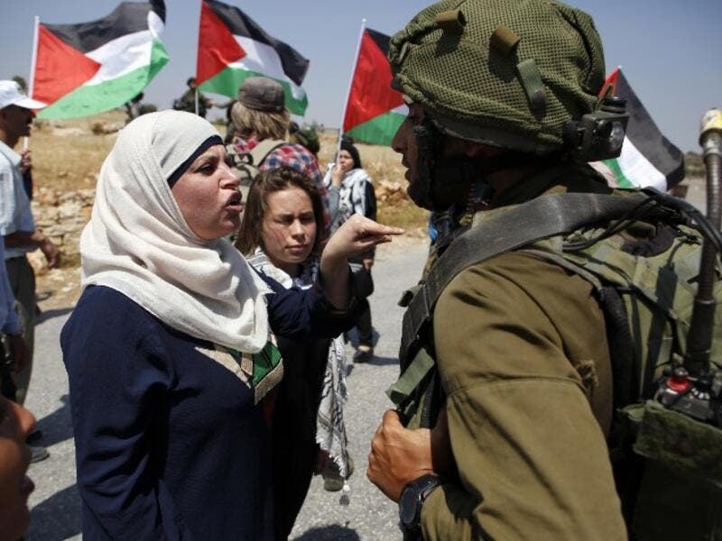 Demonstrators protest before Israeli forces West Bank village of Nabi Saleh, north of Ramallah, on May 12, 2017, after a demonstration following Friday prayers in solidarity with Palestinian prisoners on hunger strike in Israeli jails. (AFP/Abbas Momani)