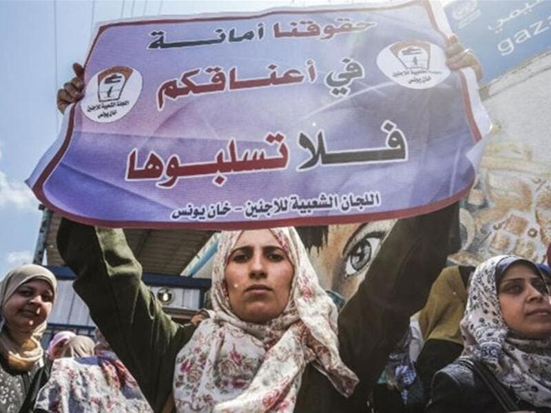 A woman holds a sign reading 'We trust you with our rights, please do not rob them' during a demonstration by UNRWA employees. (Mahmud Hams/AFP)