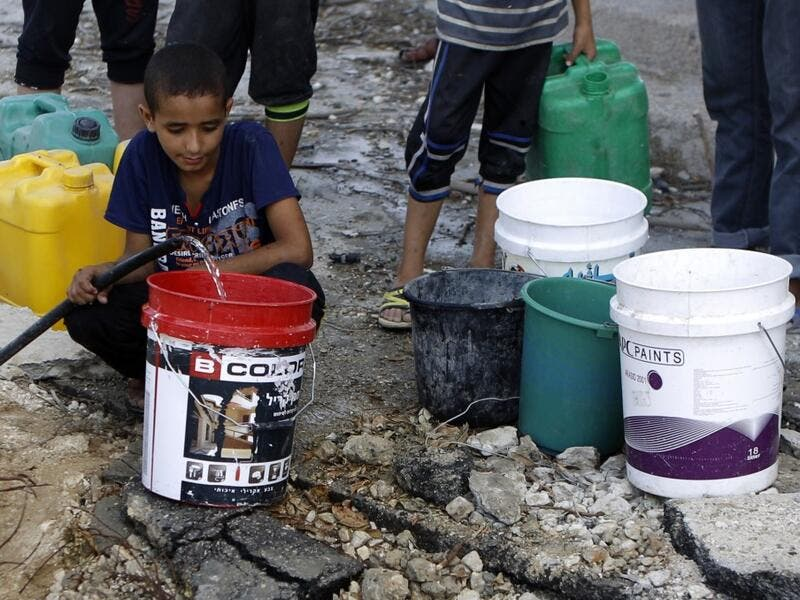Palestinians collect water from a broken pipe (Mohammed Abed/AFP)