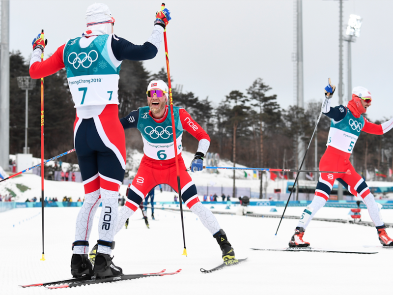 Norway's Simen Hegstad Krueger gold medallist, celebrates as countrymen silver medallist Norway's Martin Johnsrud Sundby arrive at the finish line at the end of the men's 15km + 15km cross-country skiathlon during the Pyeongchang 2018 Winter Olympic Games on February 11, 2018. (Jonathan NACKSTRAND / AFP)