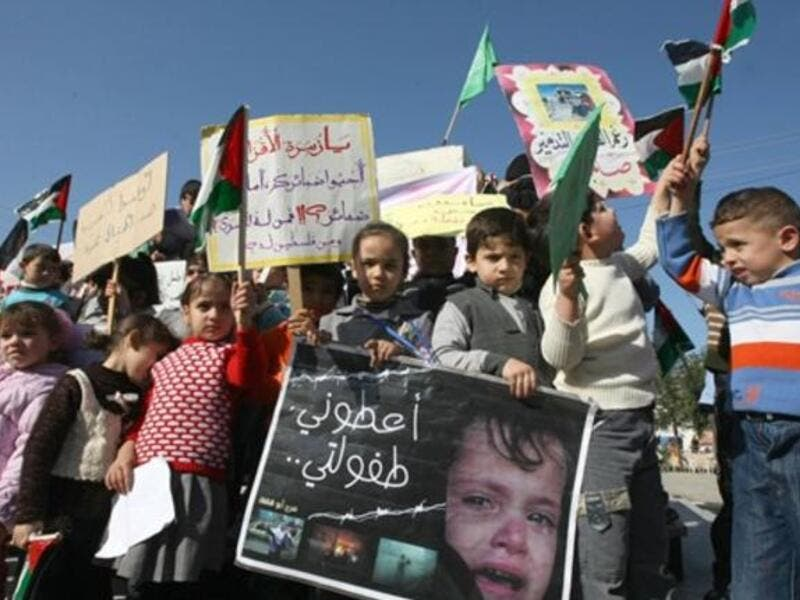 Palestinian children take part in a protest to mark the second anniversary of Israel's three-week offensive, in which over 1000 people were killed, in Jabalia refugee camp, in northern Gaza.