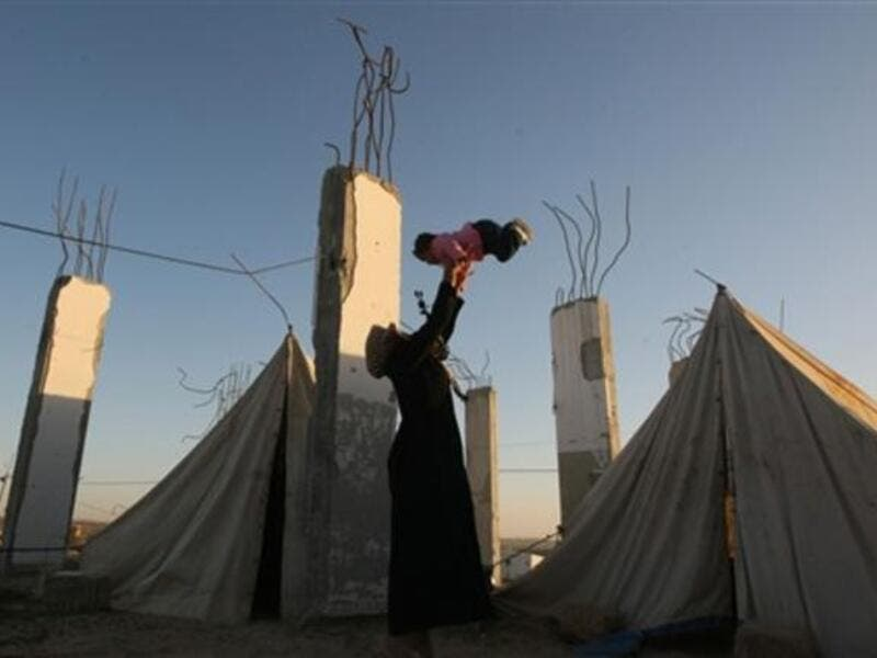 A displaced Palestinian woman carries her child outside their tent, in the Ezbet Abed Rabbo area, that was heavily destroyed during Israel's 22-day offensive on the Gaza Strip.