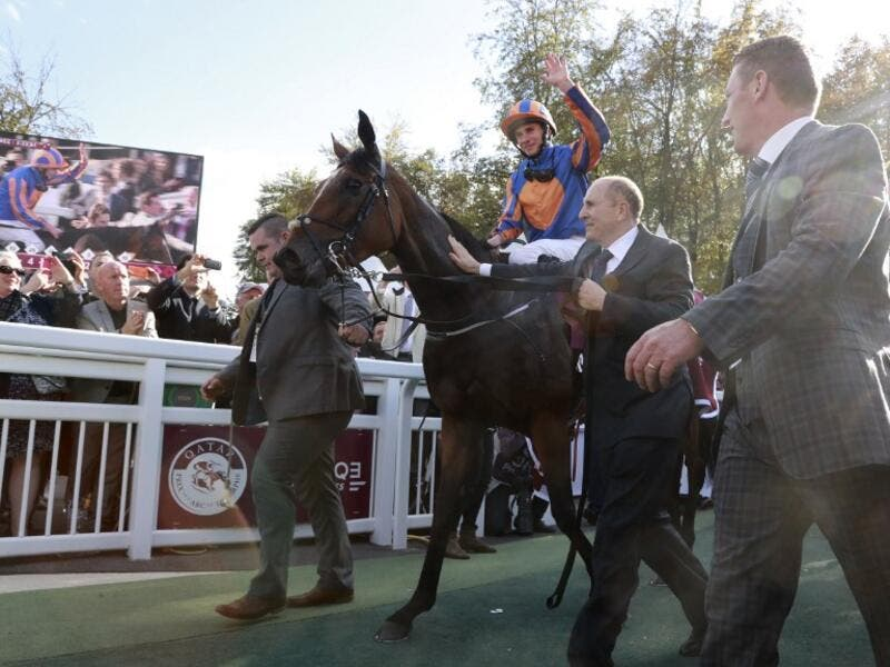 Britain's Ryan-Lee Moore (L) waves on his horse 'Found' as he celebrates winning the 95th Qatar Prix de l'Arc de Triomphe horse race at the Chantilly racecourse, northern France, on October 2, 2016.