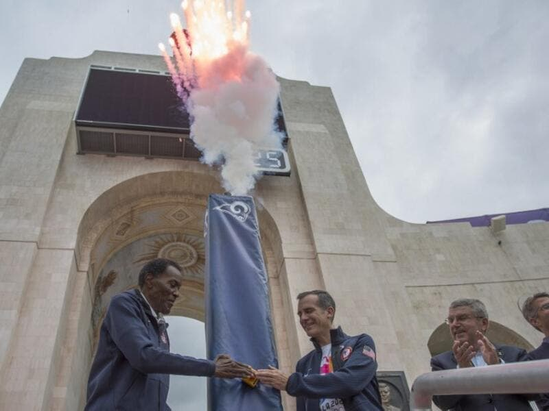 Olympic gold medalist Rafer Johnson (L), Los Angeles Mayor Eric Garcetti push the ignition switch to light the Los Angeles Memorial Coliseum's Olympic Cauldron as International Olympic Committee President Thomas Bach and LA 2028 Chairman Casey Wasserman (R) stand by on September 17, 2017 in Los Angeles.