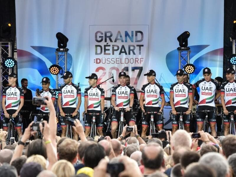 The UAE Abu Dhabi cycling team stand on stage during the team presentation ceremony in Dusseldorf, Germany, on June 29, 2017, two days before the start of the 104th edition of the Tour de France cycling race. PHILIPPE LOPEZ / AFP